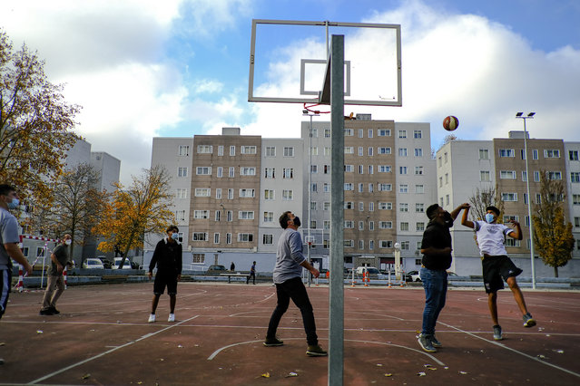 Residents keep a safe distance and wear face masks to prevent the spread of the coronavirus while playing basketball in a neighborhood outside of Pamplona, northern Spain, Friday, November 13, 2020. (Photo by Alvaro Barrientos/AP Photo)
