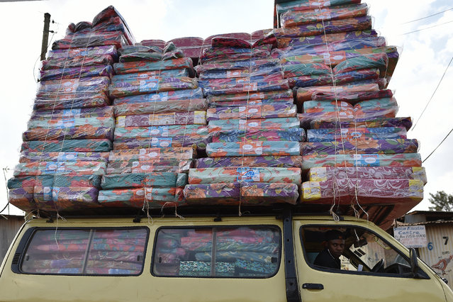 A man transports a pile of matresses held by a cord on the roof of a mini van at Ng'ando slum in the Kenyan capital, Nairobi, on January 16, 2018. (Photo by Tony Karumba/AFP Photo)