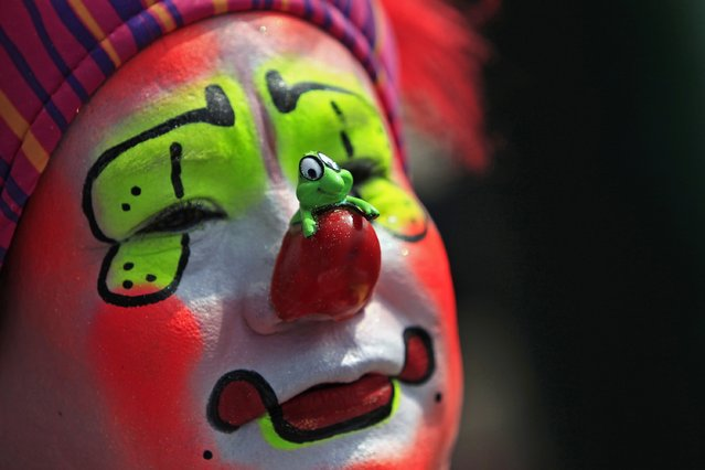 A clown looks on during the annual pilgrimage of clowns to the Basilica of Our Lady Guadalupe to pay homage to the Virgin of Guadalupe in Mexico City December 16, 2014. (Photo by Carlos Jasso/Reuters)