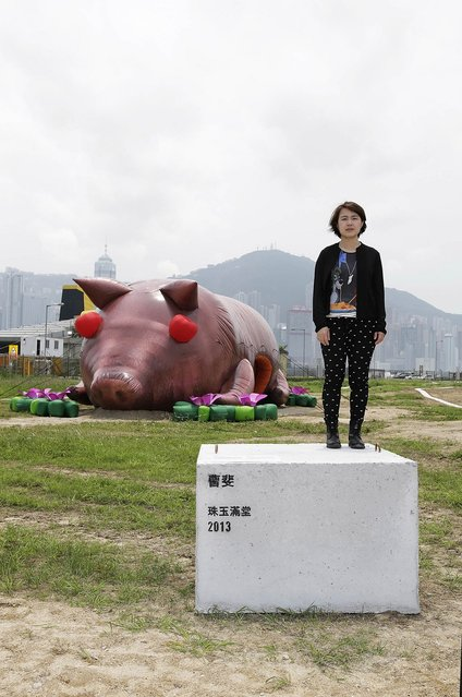 "Chinese contemporary artist Cao Fei poses with her inflatable sculpture of a pig, named ""'House of Treasures"" during the ""Inflation!"" exhibition curated by Mobile M + on April 24, 2013 in Hong Kong. The inflatable artwork is one of six on display as part of the exhibition which is open from April 25, 2013 until June 9, 2013. (Photo by Jessica Hromas)"