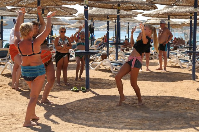 A Russian employee of a hotel teaches belly dancing to Russian tourists at the Red Sea resort of Sharm el-Sheikh, November 10, 2015. Tourism in Sharm al-Sheikh was picking up again after years of political turmoil, with so many Russians enjoying the sun and fun that local beach aerobics instructors used the visitors' own language rather than Arabic or English. (Photo by Asmaa Waguih/Reuters)
