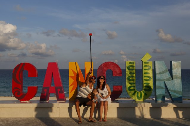 Tourists pose for a selfie in Cancun, October 13, 2015. Cancun's transformation in the 1970s from a small Caribbean fishing village into a strip of nightclubs and high-rise hotels has reduced biodiversity and polluted water resources as infrastructure struggles to keep up. (Photo by Edgard Garrido/Reuters)