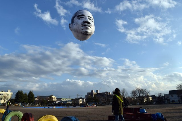 "A large balloon of a face of ""ojisan"", a middle aged man, floats in the sky above the grounds of Nishiki elementary school in Utsunomiya in Tochigi prefecture, 100km north of Tokyo on December 21, 2014. Members of art group ""Me"", meaning ""eye"" in Japanese and the Utsunomiya Museum of Art launched an art installation ""The Day an Ojisan's Face Floated in the Sky"", a 15-meter by 10-meter face balloon of the depicted man, who was auditioned in the city, looking down on his home town from the sky. (Photo by Yoshikazu Tsuno/AFP Photo)"