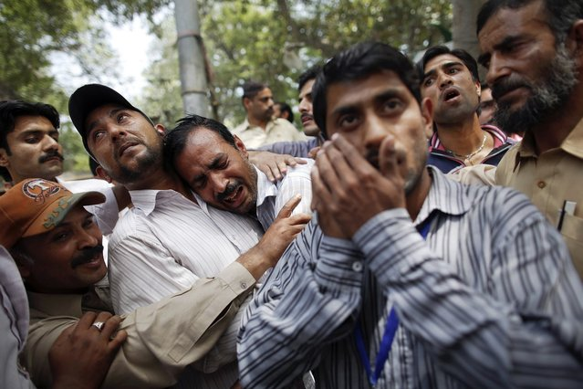 A man (C) who just left a burning building is comforted by bystanders, in central Lahore May 9, 2013. (Photo by Damir Sagolj/Reuters)