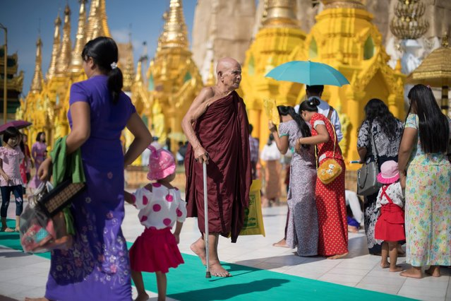 A Buddhist monk walks in the courtyard surrounding the Shwedagon Pagoda, Myanmar's most sacred Buddhist temple, in Yangon on November 26, 2017. Pope Francis arrives in Myanmar on November 27 for the first ever papal visit to the Buddhist-majority nation, whose estimated 700,000 Catholics represent just over one percent of the population. (Photo by Roberto Schmidt/AFP Photo)