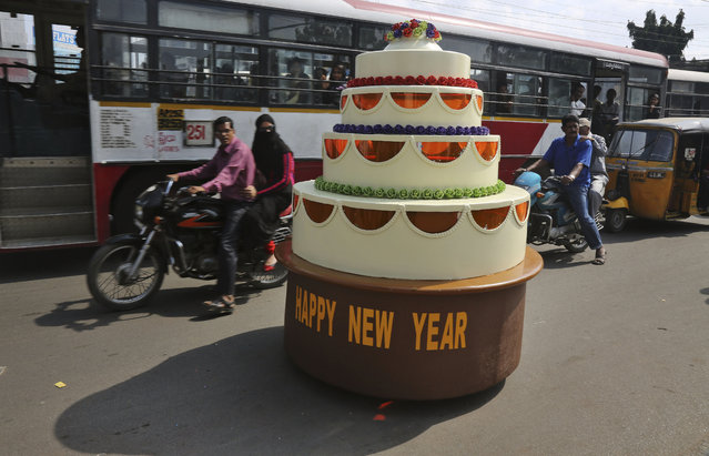 Sudhakar Yadav, the designer of a cake-shaped car, rides it on a street on New Years' eve in Hyderabad, India, Wednesday, December 31, 2014. The single seater vehicle is powered by a 100 cc engine from a road sweeping machine and can travel unto 10 kilometers per hour (6 miles per hour). (Photo by Mahesh Kumar A./AP Photo)