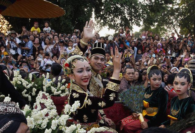 Kanjeng Pangeran Haryo Yudanegara and his wife Gusti Kanjeng Ratu Bendara wave to the crowd in a horse-drawn carriage in Yogyakarta, Indonesia, October 18, 2011. (Photo by Reuters/Beawiharta)