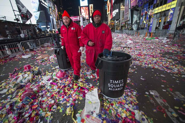 Workers prepare to clear confetti from the streets after New Year's Eve celebrations in Times Square, New York, January 1, 2015. (Photo by Keith Bedford/Reuters)