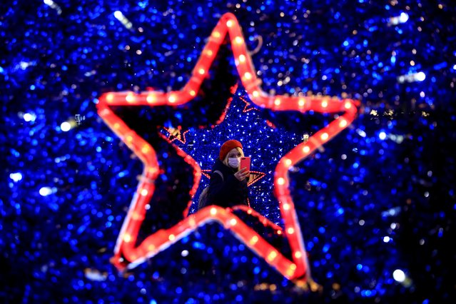 People take pictures around the Christmas decorations a few hours before the start of a two-day curfew amid the spread of the coronavirus disease (COVID-19), in Istanbul, Turkey, December 18, 2020. (Photo by Umit Bektas/Reuters)