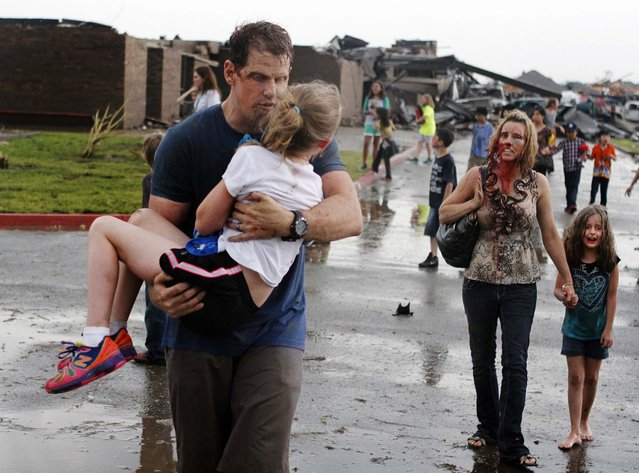 Teachers carry children away from Briarwood Elementary school after the tornado destroyed the school in south Oklahoma City. (Photo by Paul Hellstern/The Oklahoman)