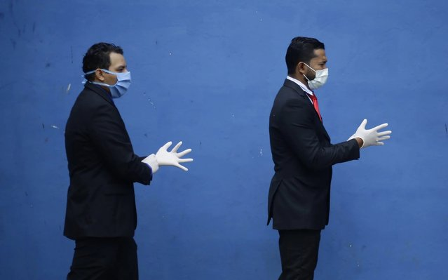 Studens wear masks and gloves prior to their graduation from El Salvador State University (UES) in San Salvador, El Salvador, 06 April 2020. A group of 71 students received the title of doctors and are ready to work during the COVID-19 pandemic, said Raul Azcunaga vice rector of UES. (Photo by Rodrigo Sura/EPA/EFE)