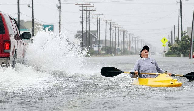 Kellie Maier laughs after getting splashed by a passing car while kayaking on water-covered Hwy 12in Kill Devil Hills, North Carolina. (Photo by Mark Wilson/Getty Images)