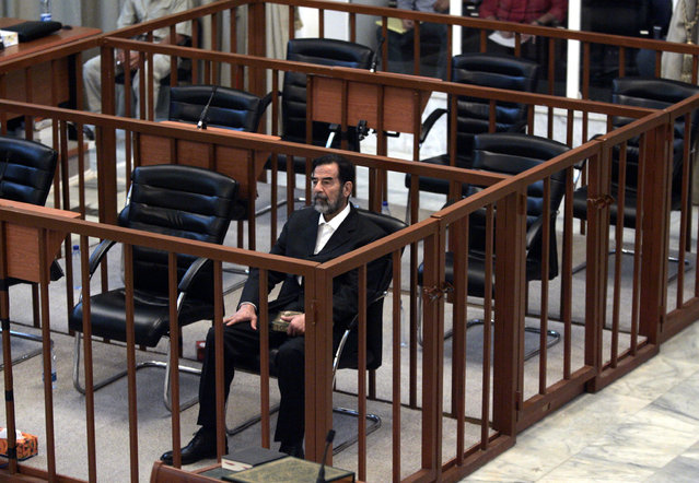 Former Iraqi President Saddam Hussein listens as his charges are read by Chief Judge Raouf Abdel-Rahman during his trial in Baghdad's heavily fortified Green Zone, Monday May 15, 2006 in Baghdad, Iraq. The chief judge formally charged Saddam Hussein on Monday with murder, torture of women and children and the illegal arrest of 399 people in a crackdown against Shiites in the 1980s, bringing the trial of the ousted Iraqi leader into a new phase. (Photo by Marco Di Lauro/AP Photo)