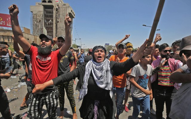 A woman shouts slogans as she takes part with Iraqi protesters in an an anti-government demonstration on Al-Jumhuriyah bridge in the capital Baghdad, on May 10, 2020. Modest anti-government rallies resumed in some Iraqi cities today, clashing with security forces and ending months of relative calm just days after Prime Minister Mustafa Kadhemi's government came to power. (Photo by Ahmad al-Rubaye/AFP Photo)