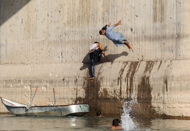 A man jumps in the Euphrates river during hot weather in Raqqa, Syria May 23, 2018. (Photo by Aboud Hamam/Reuters)