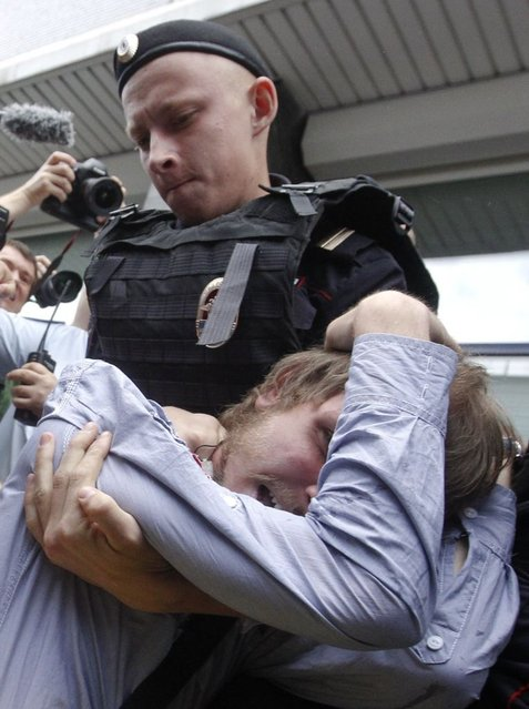 """A policeman detains a gay rights activist during a protest against a proposed new law termed by the State Duma, the lower house of Parliament, as """"against advocating the rejection of traditional family values"""" in central Moscow June 11, 2013. (Photo by Maxim Shemetov/Reuters)"""