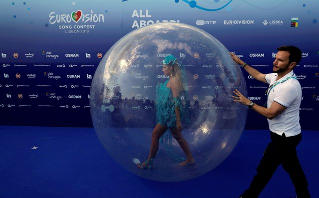 An assistant helps an actress walking in a plastic ball before the opening party for the Eurovision Song Contest at the Maat museum in Lisbon, Portugal May 6, 2018. (Photo by Rafael Marchante/Reuters)
