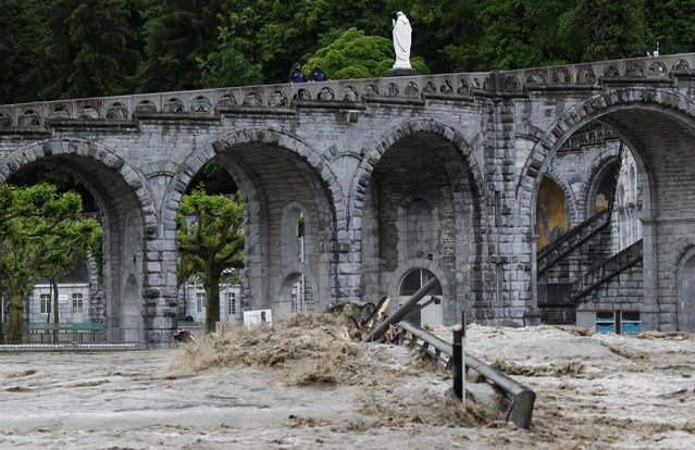 The sanctuary of Lourdes flooded, in Lourdes, southwestern France, Tuesday, June 18, 2013. French rescue services and police are evacuating hundreds of pilgrims from hotels threatened by floodwaters from a rain-swollen river in the Roman Catholic shrine town of Lourdes. (Photo by Bob Edme/AP Photo)