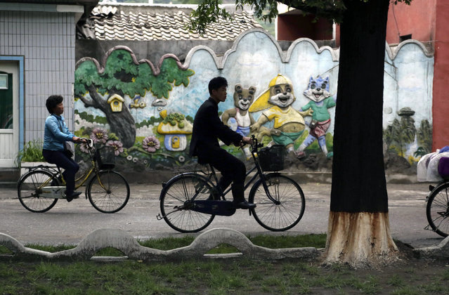 A man and women ride their bicycles past a mural in the town of Wonsan, North Korea, Friday, June 15, 2018. Wonsan is located along the eastern side of the Korean Peninsula and was one of the cities chosen to be developed into a summer destination for locals as well as tourists. (Photo by Dita Alangkara/AP Photo)