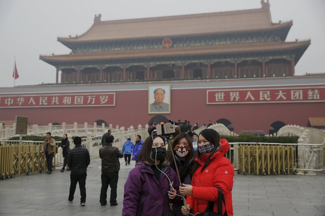"Women wearing masks protecting them from extreme smog take pictures of themselves at the Tiananmen Gate in Beijing December 8, 2015 as China's capital issues its first ever ""red alert"" for pollution. (Photo by Damir Sagolj/Reuters)"