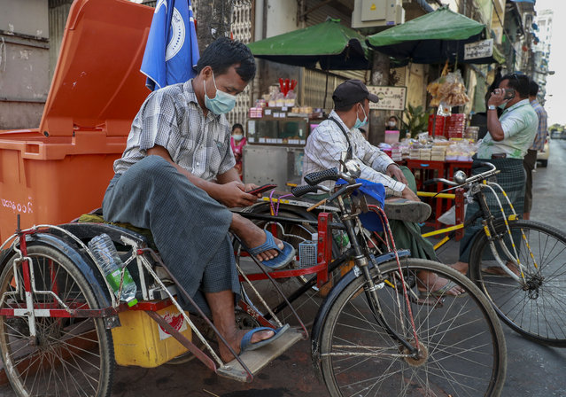 A rickshaw driver checks his mobile phone in Yangon, Myanmar, Tuesday, February 4, 2021. Myanmar's new military government has blocked access to Facebook as resistance to Monday's coup surged amid calls for civil disobedience to protest the ousting of the elected civilian government and its leader Aung San Suu Kyi. (Photo by AP Photo/Stringer)