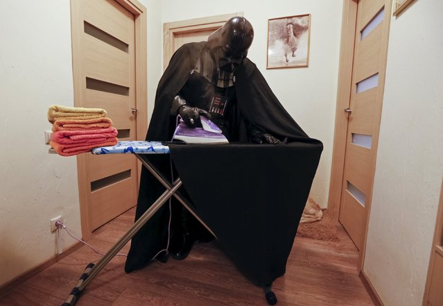 Darth Mykolaiovych Vader, who is dressed as the 'Star Wars' character Darth Vader, poses for a picture as he irons his cloak at his apartments in Odessa, Ukraine, December 2, 2015. (Photo by Valentyn Ogirenko/Reuters)