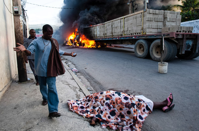 A resident expressing shock, walks by the body of rice vendor Dasilia Daniel, who was accidentally shot dead during a road rage incident as she walked to work in the Petionville suburb of Port-au-Prince, Haiti, Friday, July 19, 2013. According to a cousin of Daniel, the driver of a semi-trailer truck tapped the back of a pickup, enraging its driver, who then stepped out from his vehicle, gun in hand, and shot at the semi-truck driver, missing him and killing Daniel. Fellow vendors set the vehicles on fire in retaliation for the death of their friend. (Photo by Dieu Nalio Chery/AP Photo)