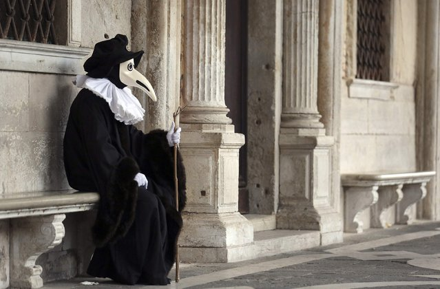 A masked reveller poses near Saint Mark's Square during the Venetian Carnival in Venice January 31, 2015. (Photo by Stefano Rellandini/Reuters)