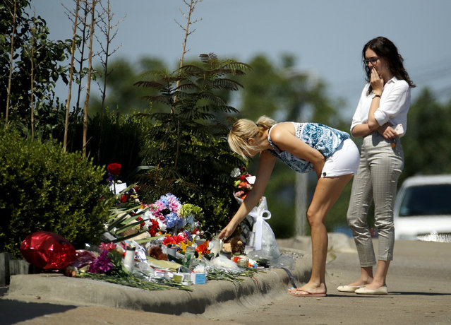 People look at a memorial in front of Ride the Ducks Saturday, July 21, 2018 in Branson, Mo. One of the company's duck boats capsized Thursday night resulting in several deaths on Table Rock Lake. (Photo by Charlie Riedel)/AP Photo
