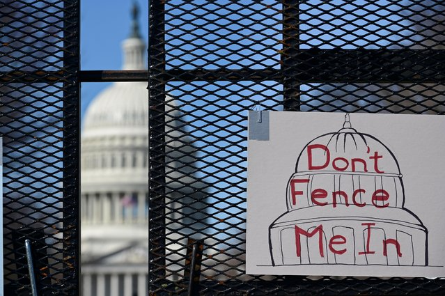 Protest signs hung by people with the group Arm in Arm DC to protest the extended presence of the surrounding security fence are seen at the U.S. Capitol in Washington, U.S. March 7, 2021. (Photo by Erin Scott/Reuters)