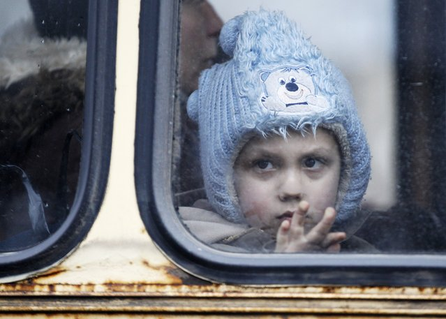 A child waits on a bus to leave the town of Debaltseve in Artemivsk, Ukraine, Tuesday, February 3, 2015. (Photo by Petr David Josek/AP Photo)