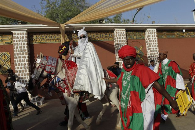 A traditional guard shouts as the new Emir of Kano Muhamadu Sanusi II (L) rides on a horse during his coronation in Kano, Kano State, February 7, 2015. (Photo by Afolabi Sotunde/Reuters)