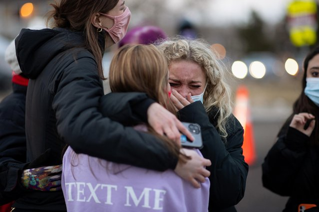 Josie Elowsky (C) cries and hugs her friend, Nirbisha Shetsha, at the site of a mass shooting at King Soopers grocery store in Boulder, Colorado, U.S. March 23, 2021. (Photo by Alyson McClaran/Reuters)