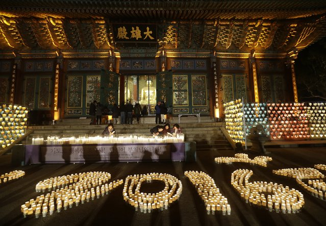 Buddhists light candles during New Year celebrations at Jogye Buddhist temple in Seoul, South Korea, early Friday, January 1, 2016. (Photo by Ahn Young-joon/AP Photo)