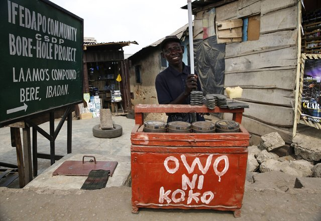 Shoe mender Mutiu Sabitiu, 40, an ethnic Yoruba Muslim, poses for a photograph at his roadside workshop in Beere district in Ibadan, southwest Nigeria January 29, 2015. Sabitiu is indifferent to the elections but hopes the best candidate emerges as president. (Photo by Akintunde Akinleye/Reuters)