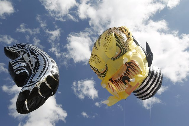 "Balloons depicting characters from the movies ""Predator"" (R) and ""Alien"" are seen in the sky at the 15th Solar Balloon Festival in Envigado, Colombia December 31, 2015. (Photo by Fredy Builes/Reuters)"