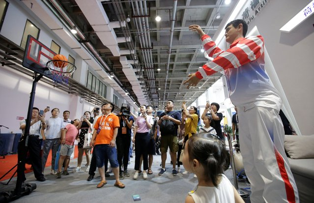 A robot replica of former NBA player Yao Ming throws a basketball at Hefu AI Group's booth at the World Robot Conference (WRC) in Beijing, China on August 15, 2018. (Photo by Jason Lee/Reuters)