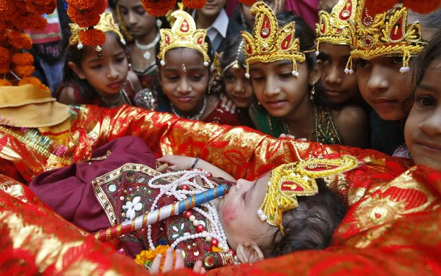 Schoolgirls dressed as Radha, the consort of Hindu Lord Krishna, look at a child dressed as Krishna during the celebrations to mark Janmashtami festival in Ahmedabad, India, on August 27, 2013. The festival, which marks the birth anniversary of Lord Krishna, will be celebrated across India. (Photo by Amit Dave/Reuters)