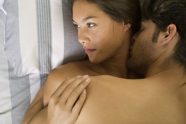 Young couple being intimate in bed, woman looking away. (Photo by Getty Images/PhotoAlto)