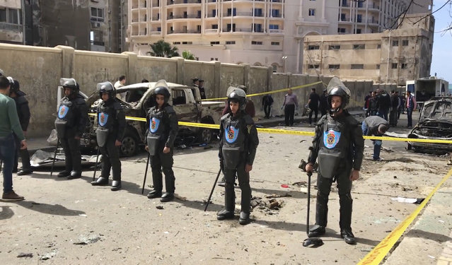 Security members stand guard as investigators search the area after a bomb placed under a nearby car exploded Saturday, March 24, 2018 in Alexandria, Egypt, as the city security chief's convoy passed by, killing at least one policeman and wounding four others, the Interior Ministry said. Local media reports said Gen. Mostafa al-Nimr survived the explosion and he was seen on a local TV channel in good condition while inspecting the area of the blast shortly after it took place. No group immediately claimed responsibility for the explosion, which happened in the vicinity of a police station in the central district of Roshdi. (Photo by Mohamed Khalil/AP Photo)