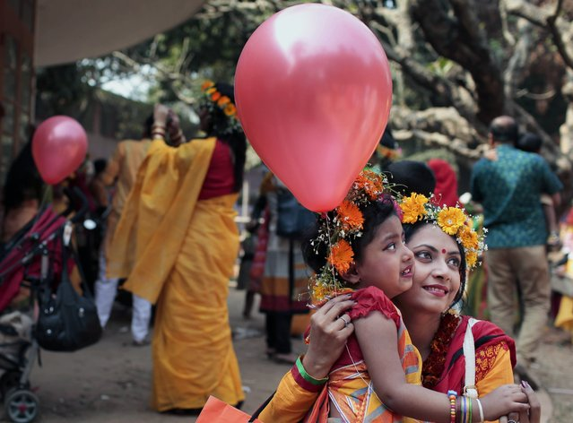 A Bangladeshi woman has her head decorated with flowers as she holds a balloon and gets a picture clicked with her child during the celebrations of the arrival of spring on the first day of Falgoon at the Dhaka University campus in Dhaka, Bangladesh, Friday, February 13, 2015. (Photo by A. M. Ahad/AP Photo)