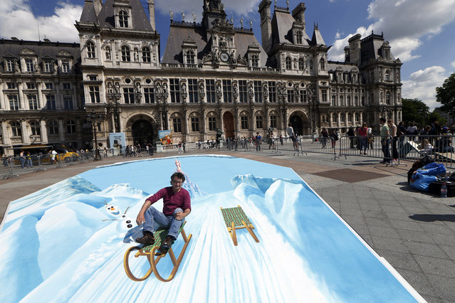 German street artist Edgar Mueller poses on his trompe l'oeil fresco painted in front of the Paris City hall as part of a communication operation for Eurodisney on May 23, 2015. (Photo by Thomas Samson/AFP Photo)