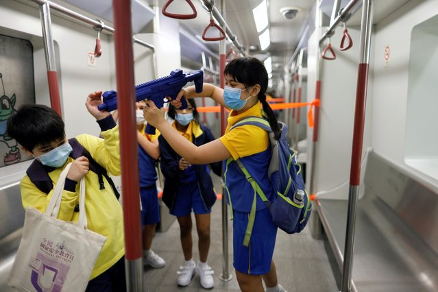 "A child plays with a mock submachine gun at a model Mass Transit Railway (MTR) station to mark the National Security Education Day at Hong Kong Police College in Hong Kong, China on April 15, 2021. The ""education day"" was organized to promote the sweeping legislation China imposed last year, marked with school activities, games and shows, and a parade by police and other services. (Photo by Tyrone Siu/Reuters)"
