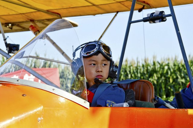 5 year-old He Yide sits in a glider before flying the plane in Guan county, Hebei province, China, on September 4, 2013. He piloted the plane, accompanied by his coach, from Guan county to Beijing Wildlife Park at a height of 150m (492 feet) and completed the flight in 35 minutes. (Photo by Reuters)