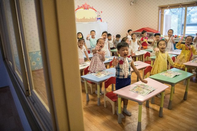 Children wave during a lesson at Gyongsang Kindergarten on August 23, 2018 in Pyongyang, North Korea. (Photo by Carl Court/Getty Images)