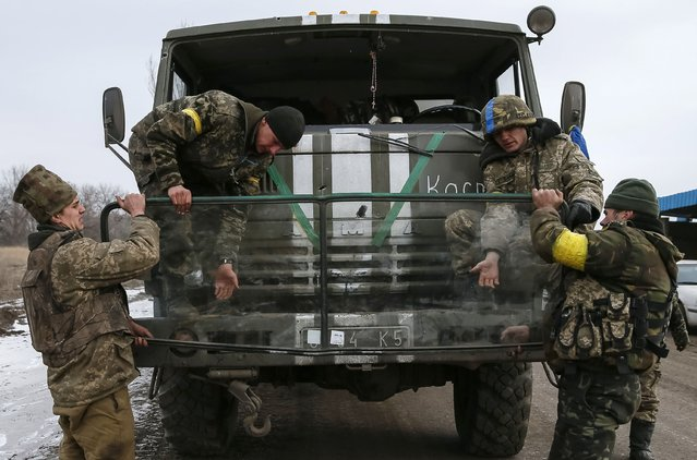 Ukrainian servicemen who fought in Debaltseve replace a window in a military vehicle before leaving for home near Artemivsk February 19, 2015. (Photo by Gleb Garanich/Reuters)