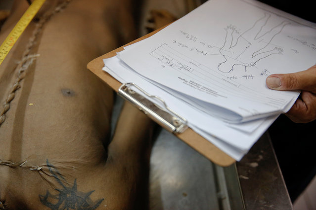 A forensics expert from the Philippines Commission on Human Rights (CHR) takes notes during an autopsy on Florjohn Cruz at Eusebio Funeral Service in Manila, Philippines October 28, 2016. (Photo by Damir Sagolj/Reuters)