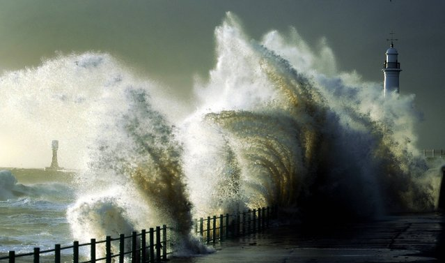 "Strong winds whip up huge waves battering the coast at Seaburn near Sunderland, as Britain experiences a ""short, sharp shock"" of colder temperatures after the Indian summer, on October 10, 2013. (Photo by Owen Humphreys/PA Wire)"