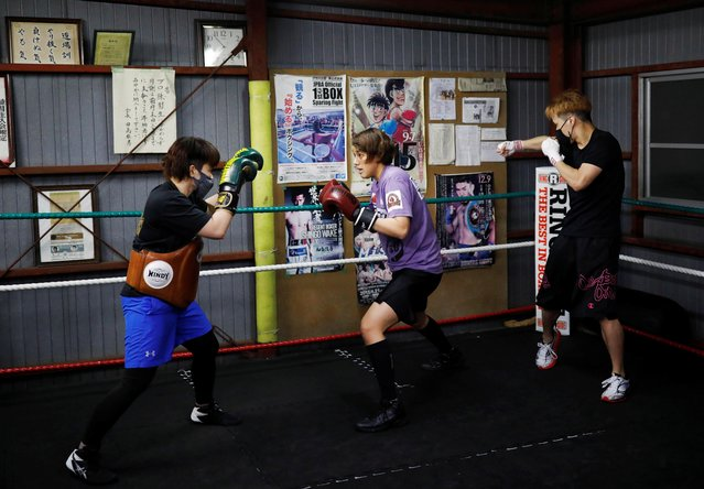 """Arisa Tsubata, 27, a nurse and a boxer, trains with her trainer Tomoko Okada at Tajima boxing gym in Sayama, Saitama Prefecture, Japan, April 15, 2021. Tsubata has trained around her work shifts for over a year to prepare for a final Olympic boxing qualifier in the hope of making it to the Tokyo Games this summer. That dream was shattered earlier this year after the International Olympic Committee (IOC) decided to cancel the boxing qualifiers due to take place in June and to allocate spots based on the rankings of recent years instead. """"'Why did I aim for the Olympics when the coronavirus happened?' I asked myself"""", Tsubata said, also wondering, """"who knew the coronavirus pandemic would come at this time?"""". (Photo by Kim Kyung-Hoon/Reuters)"""