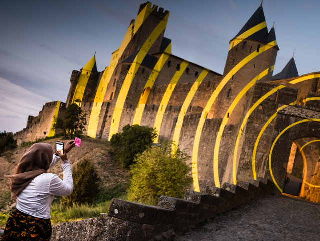 """""""Art installation by Felice Varini on the medieval walls of Carcassonne, France. At sunset there was a crowd of people where the concentric circles aligned. I was intrigued by this lady sending a hand-written message on a pink Post-it note"""". (Photo by Katy Bridgestock/The Guardian)"""